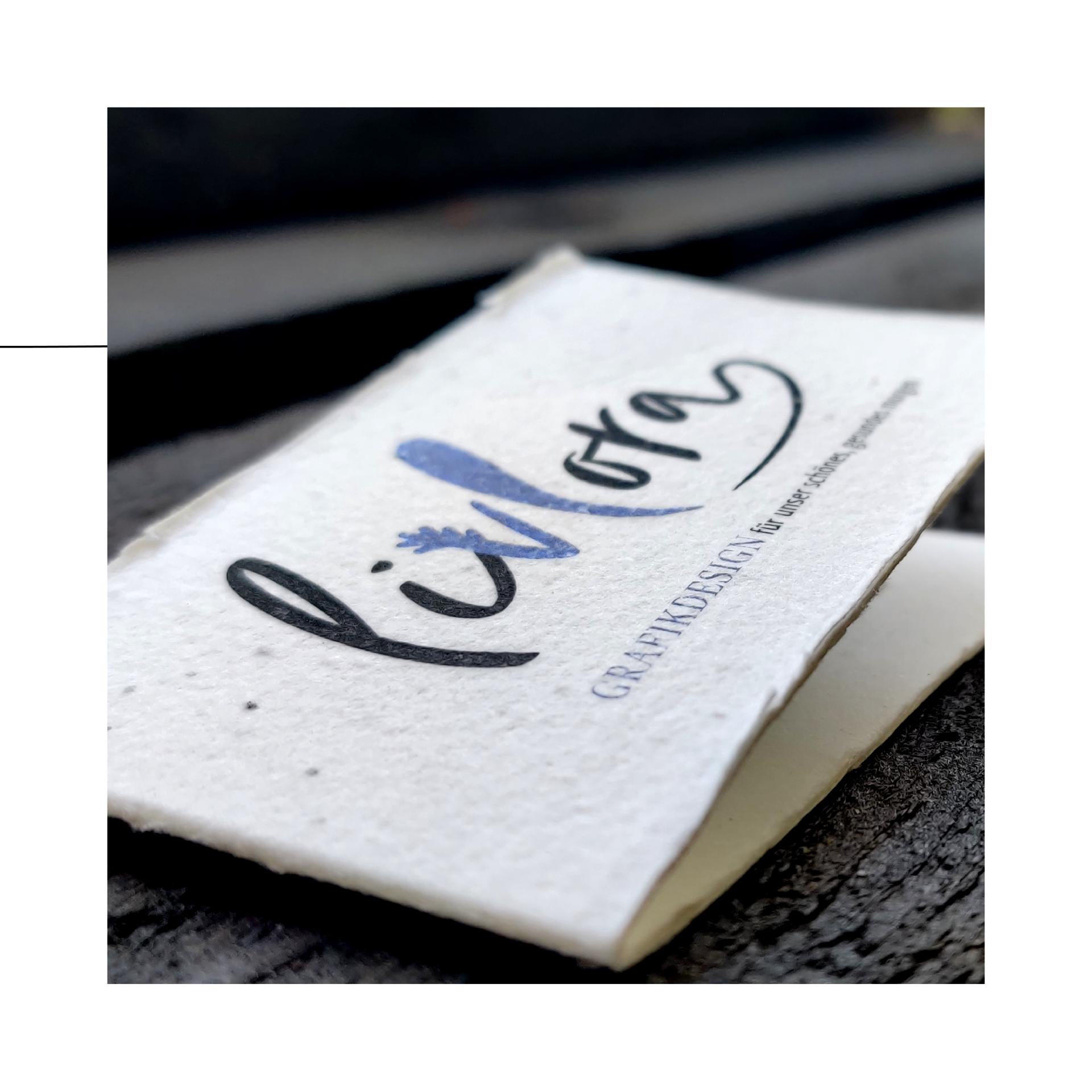 """foto von livlora visitenkarte, zugeklappt. die karte ist aus saat-papier, hat eine raue oberfläche & ausgefranste kanten. zu sehen ist das logo """"livlora"""" & darunter der text: """"grafikdesign für unser schönes, gesundes morgen"""""""